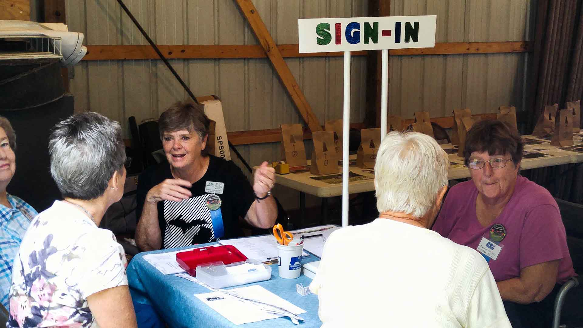 The sign-in table with Phyl Miner and Marianne Folkerts. Joy Kruse is to the far left. Not sure who the others with backs to us are.