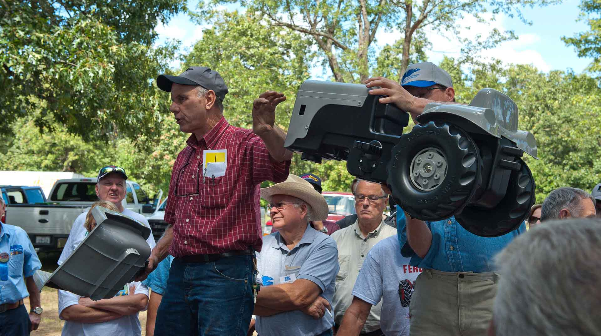 """Steve Bieberich and Brent Holoway holding up the Gratass """"The Little Grey Fergie"""" Pedal Tractor."""