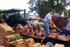 The Ozark Steam Engine Association cutting cedar shingles using a steam tractor.